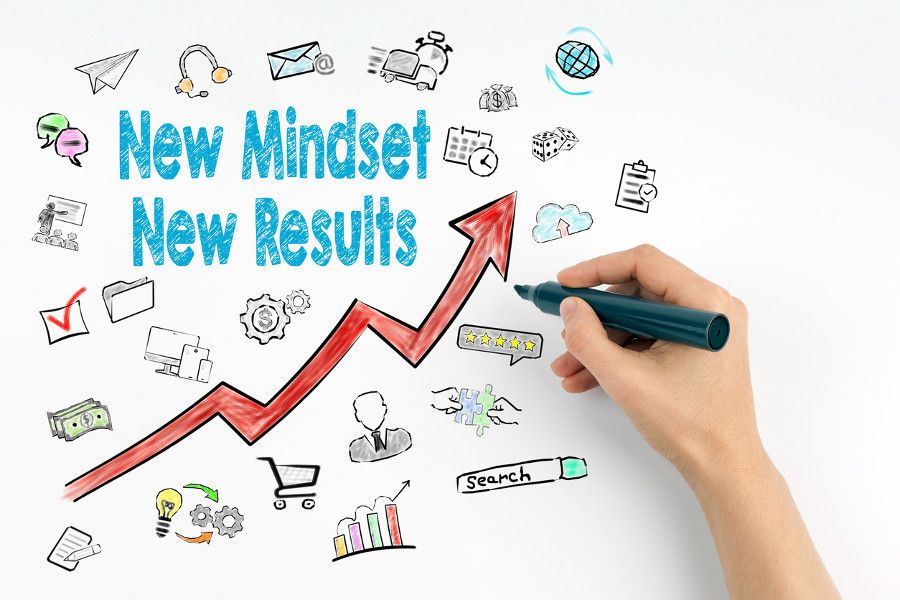 "Illustration of hand writing out ""New Mindset, New Results"" as it relates to The Momentum Game."